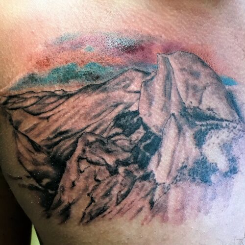 mountain scene chest tattoo by Makeba Ische at Cactus Tattoo in Mankato