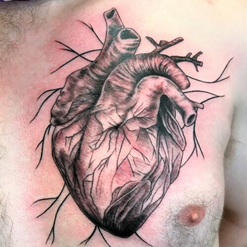 realistic heart chest tattoo by Makeba Ische at Cactus Tattoo in Mankato